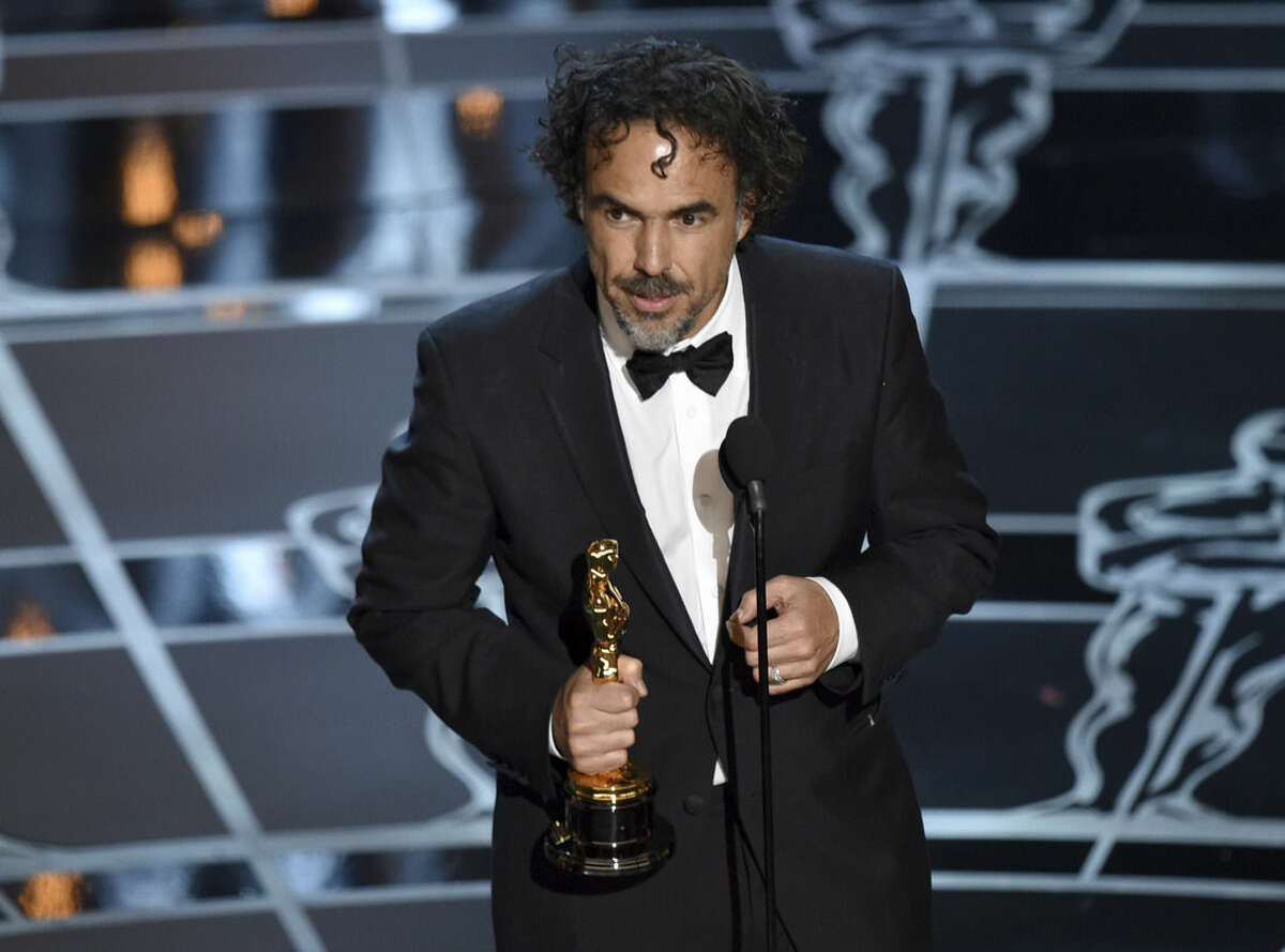 """Alejandro G. Inarritu accepts the award for best director for """"Birdman or (The Unexpected Virtue of Ignorance)"""" at the Oscars on Sunday, Feb. 22, 2015, at the Dolby Theatre in Los Angeles. (Photo by John Shearer/Invision/AP)"""