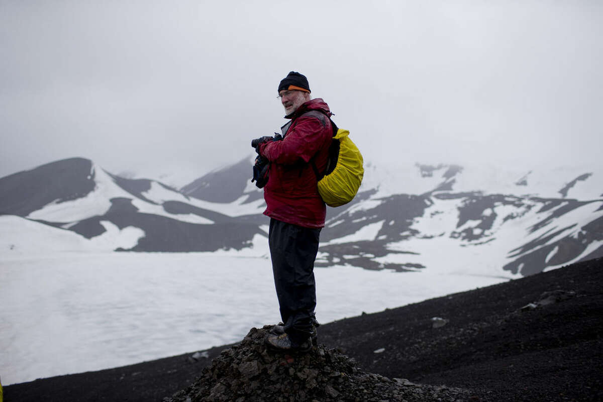 """In this Jan. 24, 2015 photo, Peter Convey, a senior research professor with the British Antarctic Survey searches for samples on Deception Island, in the South Shetland Islands archipelago, Antarctica. """"I was last here 10 years ago,"""" Convey said. """"And if you compare what I saw back then to now, the basic difference due to warming is that the permanent patches of snow and ice are smaller. They're still there behind me, but they're smaller than they were. Year on year on year, that is what we're seeing across the entire West Antarctic Peninsula region. Small patches of snow are getting smaller, bigger patches of ice, which would eventually develop into glaciers are retreating as well."""" (AP Photo/Natacha Pisarenko)"""
