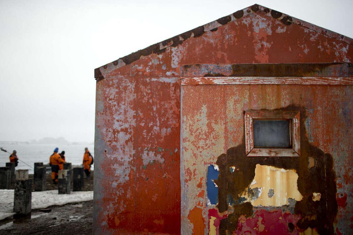 In this Jan. 24, 2015 photo, scientists walk near a Chilean shelter in Robert Island, in the South Shetland Islands archipelago, Antarctica. NASA satellite measurements calculate that since 2004, Antarctica has lost 130 billion tons of ice (118 billion metric tons) each year. (AP Photo/Natacha Pisarenko)