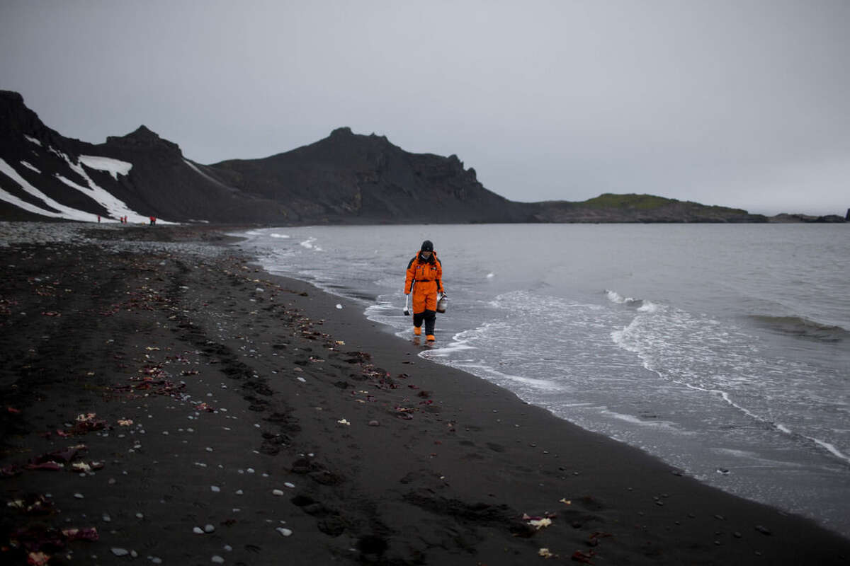 """In this Jan. 26, 2015 photo, Wenjun Li, a marine chemist from China, walks along the beach in search of samples in Punta Hanna, Livingston Island, South Shetland Islands archipelago, Antarctica. Parts of Antarctica are melting so rapidly it has become """"ground zero of global climate change without a doubt,"""" said Harvard geophysicist Jerry Mitrovica. (AP Photo/Natacha Pisarenko)"""