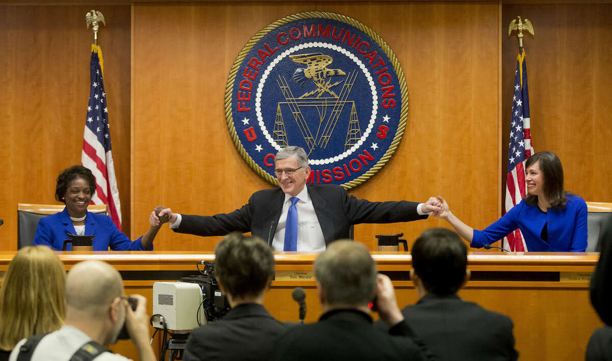 """Federal Communication Commission (FCC) ChairmanTom Wheeler, center, joins hands with FCC Commissioners Mignon Clyburn, left, and Jessica Rosenworcel, before the start of their open hearing in Washington, Thursday, Feb. 26, 2015. Internet service providers like Comcast, Verizon, AT&T, Sprint and T-Mobile would have to act in the """"public interest"""" when providing a mobile connection to your home or phone, under new rules being considered by the Federal Communications Commission. The rules would put the Internet in the same regulatory camp as the telephone, banning providers from """"unjust or unreasonable"""" business practices. (AP Photo/Pablo Martinez Monsivais)"""