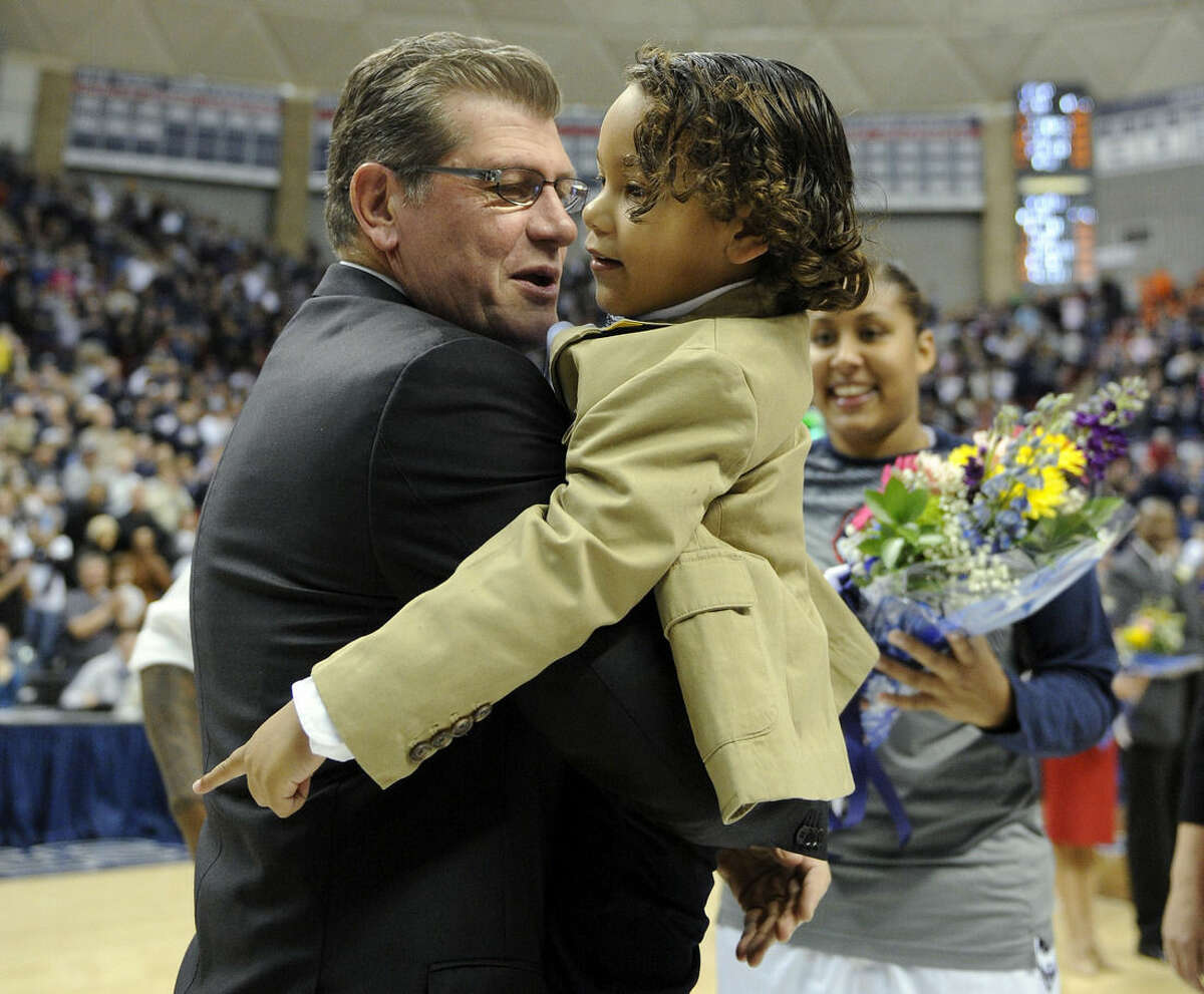 Connecticut head coach Geno Auriemma, left, hugs Xander Mosqueda-Lewis as his sister Kaleena looks on during senior day celebrations before an NCAA college basketball game against Memphis in Storrs, Conn., Saturday, Feb. 28, 2015. (AP Photo/Fred Beckham)