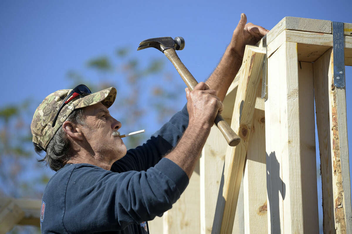 In this Feb. 13, 2015 photo, construction worker David Rager, 53, frames the upper floor of a two-story custom home being built in Orlando, Fla. As construction jobs return in some regions, competition for skilled labor is heating up.(AP Photo/Phelan M. Ebenhack)
