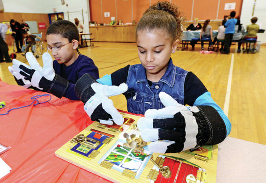 Hour photo / Erik TrautmannJefferson Elementary School third-graders Amaya Jones and Leo Reyes don gloves to make intricate tasks more difficult Thursday during the Norwalk SPED Partners and the Norwalk Public Schools program, Walk in My Shoes, that helps typical students understand the challenges special education students face. / (C)2013, The Hour Newspapers, all rights reserved