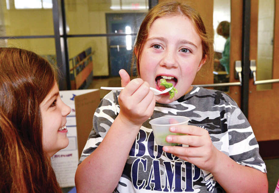 Jefferson Elementary School 3rd grader Sarah Signore takes a bite of school grown salad after 250 students 'graduate' from a groundbreaking three year health, fitness and nutrition program run in partnership with Pepperidge Farm, Norwalk Hospital and Norwalk Health Department in a program called Project L.E.A.N. (Learning with Energy from Activity and Nutrition) Wednesday . Hour photo / Erik Trautmann / (C)2013, The Hour Newspapers, all rights reserved