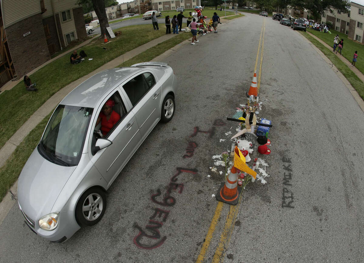 """FILE - In this Aug. 15, 2014, file photo, a car drives past a memorial in the middle of the street where Michael Brown was shot by police in Ferguson, Mo. Six months after 18-year-old Michael Brown died in the street in Ferguson, Missouri, the Justice Department is close to announcing its findings in the racially charged police shooting that launched """"hands up, don't shoot"""" protests across the nation. (AP Photo/Charlie Riedel, File)"""