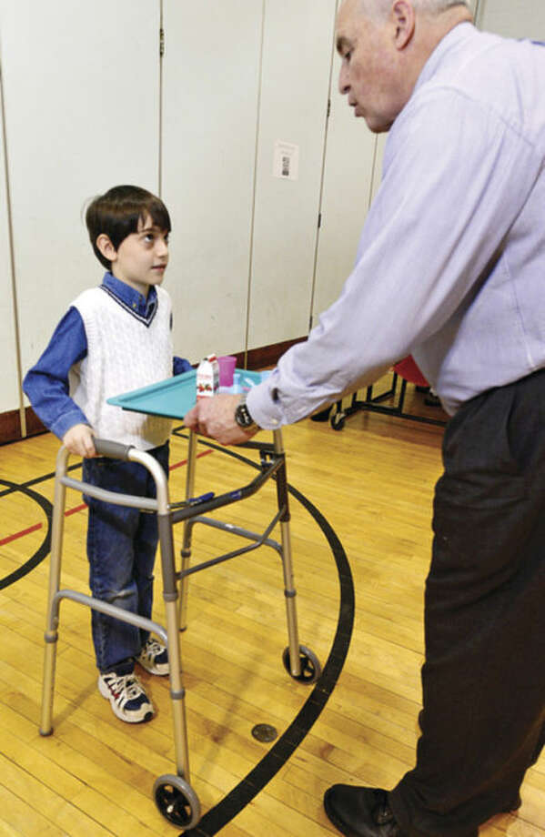 Jefferson Elementary School 3rd grader Harrison Perone receives a walker and a tray from volunteer Jeffry Spahr Thursday during the Norwal Sped Partners and the Norwalk Public Schools program, Walk in My Shoes, that helps typical students understand the challenges special education students face.Hour photo / Erik Trautmann