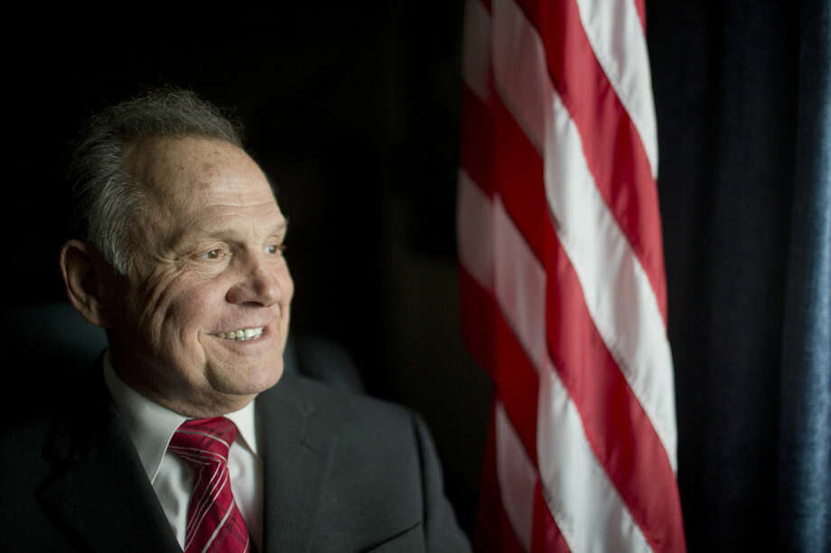 FILE - In this Feb. 17, 2015, file photo, Alabama Chief Justice Roy Moore poses in front the the American flag in Montgomery, Ala. The Alabama Supreme Court on Tuesday, March 3, 2015 ordered the state's probate judges to stop issuing marriage licenses to gay couples, a decision that flies in the face of numerous rulings by federal judges in Alabama and other states across the country who have said banning gay marriage violates the U.S. Constitution. (AP Photo/Brynn Anderson, file)