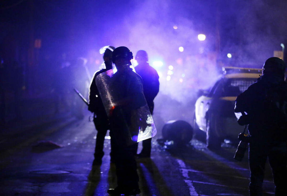"""FILE - In this Nov. 25, 2014 file photo, police officers watch protesters as smoke fills the streets in Ferguson, Mo. after a grand jury's decision in the fatal shooting of Michael Brown. Six months after 18-year-old Michael Brown died in the street in Ferguson, Missouri, the Justice Department is close to announcing its findings in the racially charged police shooting that launched """"hands up, don't shoot"""" protests across the nation. (AP Photo/Charlie Riedel, File)"""