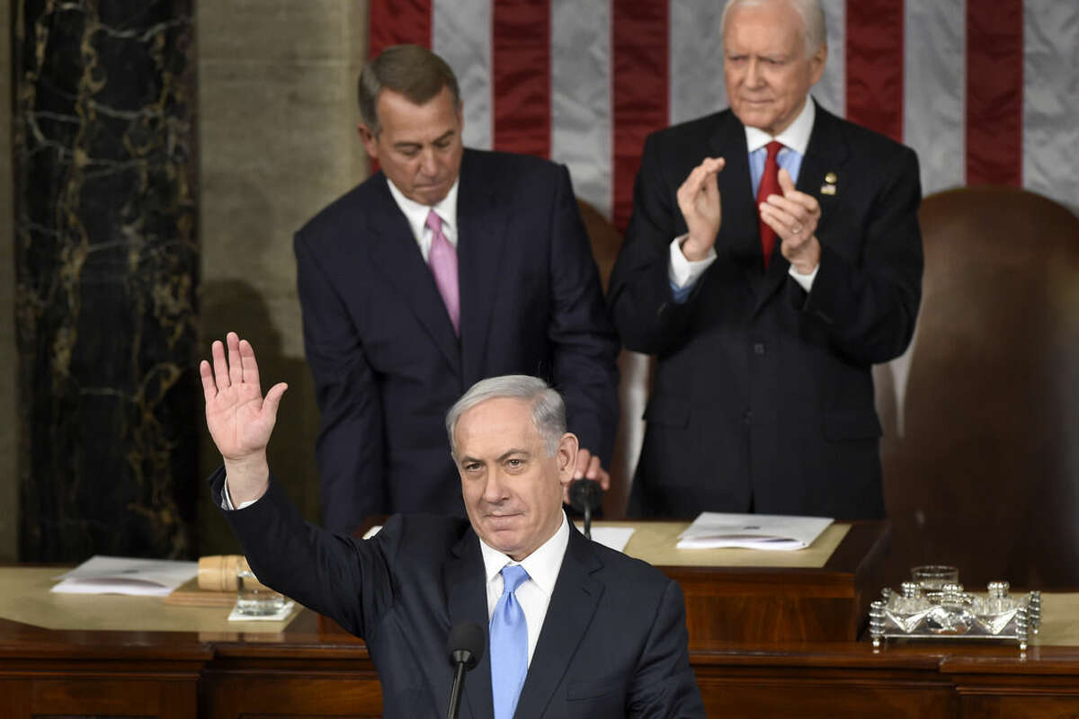 """Israeli Prime Minister Benjamin Netanyahu waves as he speaks before a joint meeting of Congress on Capitol Hill in Washington, Tuesday, March 3, 2015. In a speech that stirred political intrigue in two countries, Netanyahu told Congress that negotiations underway between Iran and the U.S. would """"all but guarantee"""" that Tehran will get nuclear weapons, a step that the world must avoid at all costs. House Speaker John Boehner of Ohio, left, and Sen. Orrin Hatch, R-Utah, are behind the prime minister. (AP Photo/Susan Walsh)"""