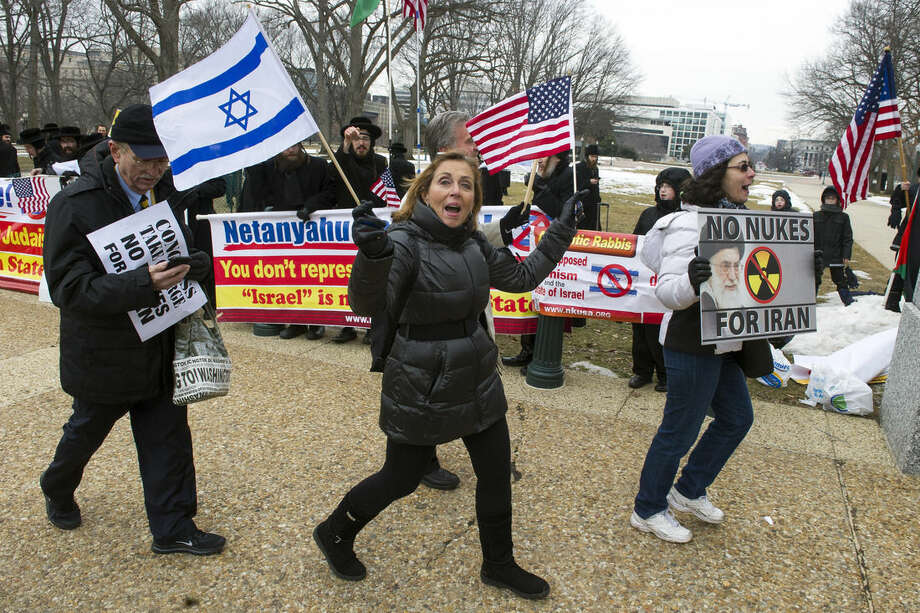 Pro Israel demonstrators walks past anti-Israel demonstrators on Capitol Hill in Washington, Tuesday, March 3,2015, while Israeli Prime Minister Benjamin Netanyahu addressed a Joint Session of Congress. (AP Photo/Cliff Owen)