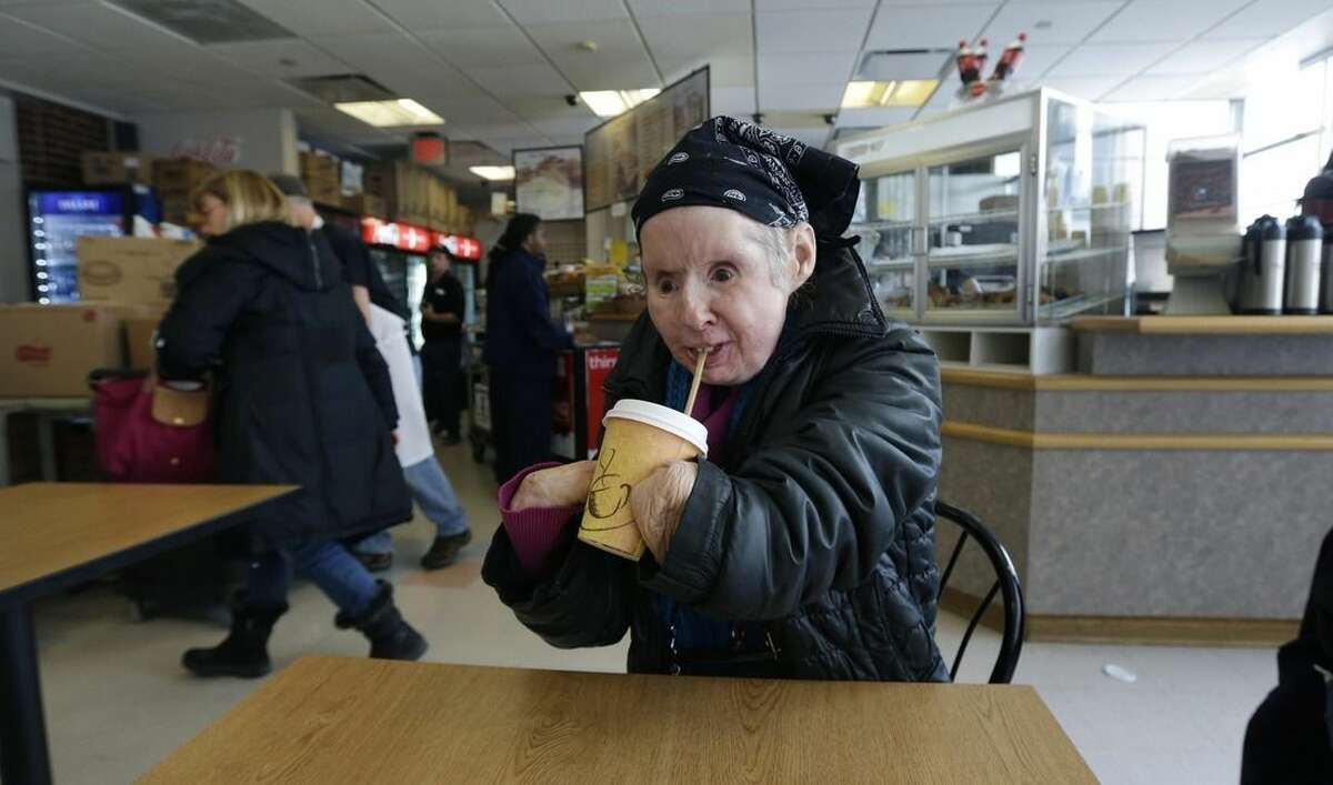 In this Tuesday March 3, 2015 photograph, Charla Nash drinks a cup of hot coffee through a straw while visiting a cafe in Boston. Nash, who is blind, lost her face, eyes and hands after being mauled by a chimpanzee in 2009. The military is hoping the information they learn from Nash's rehabilitation can help young, seriously disfigured soldiers returning from war. (AP Photo/Charles Krupa)