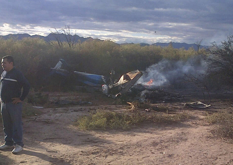 A man stands near one of two helicopters that crashed near Villa Castelli in the La Rioja province of Argentina, Monday, March 9, 2015. Two helicopters with passengers who were filming a documentary crashed Monday in the remote area of northwest Argentina, killing all 10 people on board both aircrafts, authorities said. (AP Photo/Jose Alamo)