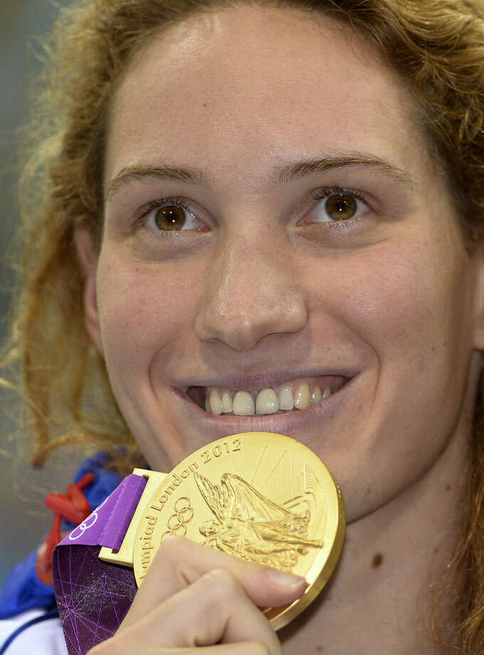 """FILE .- In this Sunday, July 29, 2012 file photo France's Camille Muffat celebrates with her gold medal for the women's 400-meter freestyle swimming final at the Aquatics Centre in the Olympic Park during the 2012 Summer Olympics in London. Two helicopters carrying passengers filming the popular European reality show """"Dropped"""" crashed Monday, March 9, 2015 in a remote area of northwest Argentina, killing all passengers on board including Muffat, according to authorities. (AP Photo/Mark J. Terrill/File)"""