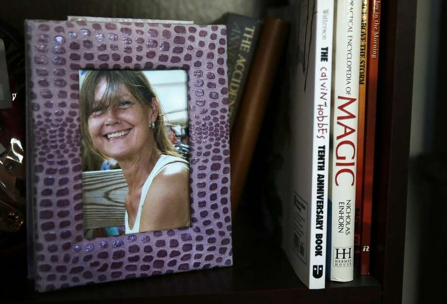 In this Friday, Feb. 20, 2015 photograph, a framed photograph of Charla Nash, taken before she was attacked by a chimpanzee, sits on a bookshelf at her second-story apartment in Boston. The Department of Defense is following Nash's progress, after funding her full-face transplant surgery in 2011. Nash lost her face, eyes and hands after being mauled by her boss's pet in 2009. The military is hoping the information they learn from Nash's rehabilitation can help young, seriously disfigured soldiers returning from war. (AP Photo/Charles Krupa)