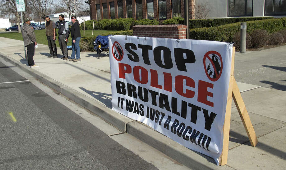 FILE - In this Feb. 18, 2015 file photo, a protest sign is displayed in front of City Hall in Pasco, Wash., the city where Antonio Zambrano-Montes, an unarmed man who was running away from police at a crowded intersection, was fatally shot by police on Feb. 10, 2015. Ferguson, Mo., has become an emblem of the tensions between minorities and police departments nationwide since Darren Wilson, a white officer, shot and killed Michael Brown, an unarmed black teenager, last summer. A U.S. Justice Department report released the first week of March, 2015, cleared Wilson of criminal wrongdoing. Though the study centered on Ferguson, its findings have resonated nationwide as residents in some communities across the country say they feel they face the same struggles with their police departments and city leadership. (AP Photo/Nicholas K. Geranios, File)