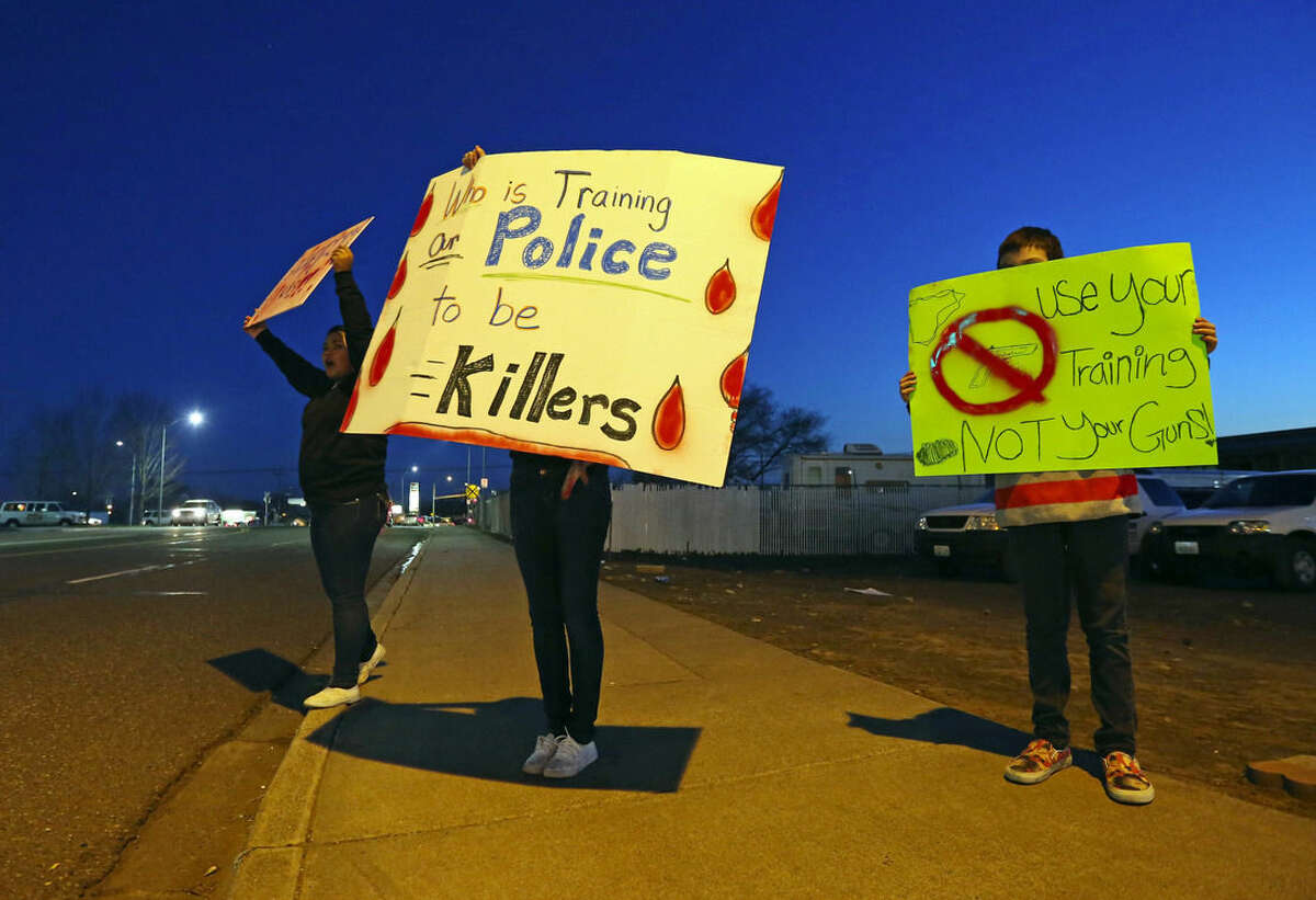 FILE - In this Feb. 12, 2015 file photo, demonstrators gather at the corner where the shooting of Antonio Zambrano-Montes took place in Pasco, Wash. Ferguson, Mo., has become an emblem of the tensions between minorities and police departments nationwide since Darren Wilson, a white officer, shot and killed Michael Brown, an unarmed black teenager, last summer. A U.S. Justice Department report released the first week of March, 2015, cleared Wilson of criminal wrongdoing. Though the study centered on Ferguson, its findings have resonated nationwide as residents in some communities across the country say they feel they face the same struggles with their police departments and city leadership. (AP Photo/The Seattle Times, Alan Berner, File) SEATTLE OUT; USA TODAY OUT; MAGS OUT; TELEVISION OUT; NO SALES; MANDATORY CREDIT TO BOTH THE SEATTLE TIMES AND THE PHOTOGRAPHER