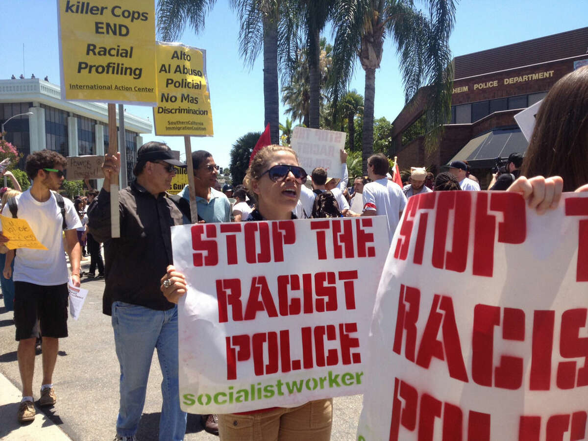 FILE - In this July 29, 2012 file photo, protesters demonstrate outside he Anaheim, Calif., Police Department headquarters over a string of recent fatal police shootings in Anaheim. Ferguson, Mo., has become an emblem of the tensions between minorities and police departments nationwide since Darren Wilson, a white officer, shot and killed Michael Brown, an unarmed black teenager, last summer. A U.S. Justice Department report released the first week of March, 2015, cleared Wilson of criminal wrongdoing. Though the study centered on Ferguson, its findings have resonated nationwide as residents in some communities across the country say they feel they face the same struggles with their police departments and city leadership. (AP Photo/The Orange County Register, Stuart Palley, File) MAGS OUT; LOS ANGELES TIMES OUT