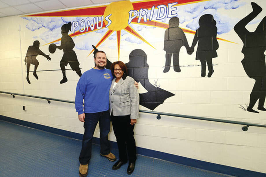 Hour photo / Erik Trautmann 8th grade social studies teacher, Patrick Jeanetti, gives well wishes to Linda Sumpter, principal of Ponus Ridge Middle School, will retire in June after 15 years.