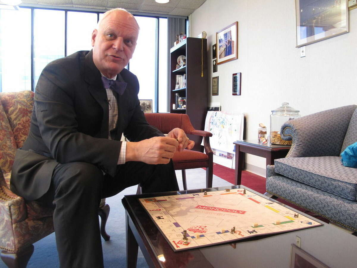 In this March 11, 2015 photo, Atlantic City, N.J. Mayor Don Guardian holds a game piece from the Monopoly board game in his City Hall office. The game, which turns 80 on March 19, 2015, is based on the real-life streets of Atlantic City. (AP Photo/Wayne Parry)