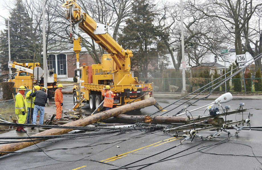 @Cutline Byline:Hour photo/Erik TrautmannEversource workers fix a utlity pole that was felled by a car on Quintard Ave and Route 136 Tuesday.
