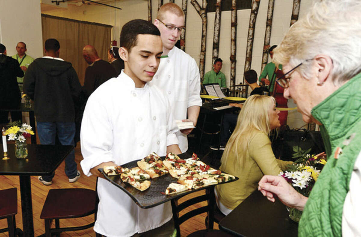 """Hour photo / Erik Trautmann Norwalk High School students Miguel Argueta and Michael Stein serve up pizza slices to school administrative assistant Pattrry Yarnold during the grand opening and ribbon cutting of the new Culinary Arts Café. The café will be a """"learning center"""" providing real world experiences and hands on activities for the students of Norwalk High."""
