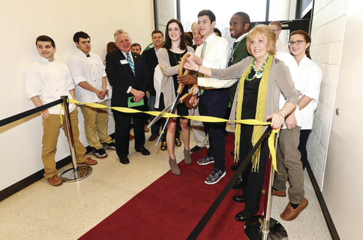 """Hour photo / Erik Trautmann Norwalk High School Housemaster Carol Marinaccio, Principal Reginald Roberts and seniors Anthony Granchelli and Claire Rudden cut the ribbon cutting for the grand opening of the new Culinary Arts Café. The café will be a """"learning center"""" providing real world experiences and hands on activities for the students of Norwalk High."""