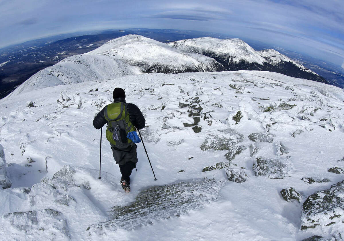 In this Tuesday, March 10, 2015 photo, a hiker leaves the summit of Mount Washington, New Hampshire. The snow-covered peaks of the northern presidential range can be seen in the distance. They are, from left, Mounts Clay, Jefferson, Adams and Madison, (AP Photo/Robert F. Bukaty)