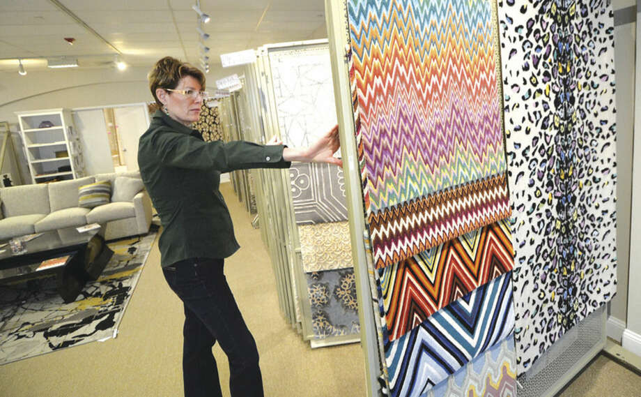 Hour Photo/Alex von Kleydorff Stark Showroom Manager Priscilla Cronin flips through some of the many custom carpet samples such as the colorful ones from designer Missoni