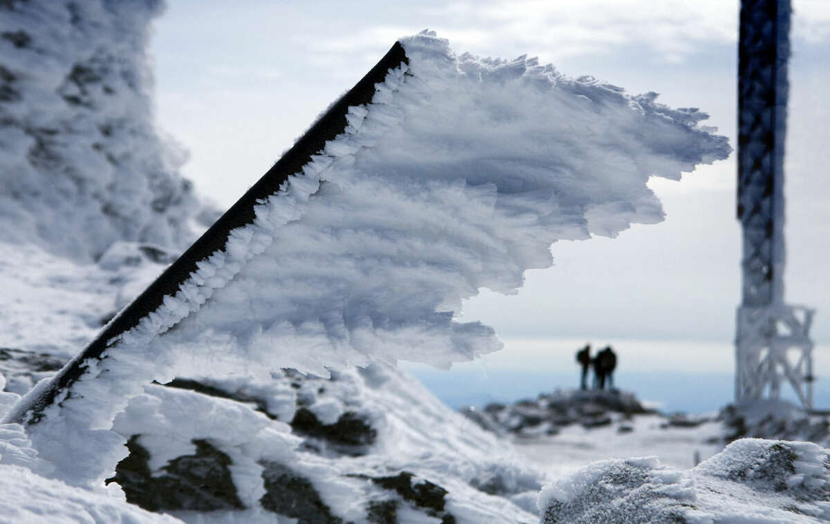 In this Tuesday, March 10, 2015 photo, rime ice extends horizontally from a metal pole at the summit of Mt. Washington, in New Hampshire. Rime ice forms in the direction of the wind driven fog that often blows across the summit at hurricane force. (AP Photo/Robert F. Bukaty)