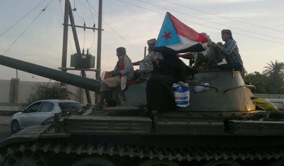 Militiamen loyal to President Abed Rabbo Mansour Hadi ride on a tank on a street in Aden, Yemen, Thursday, March 19, 2015. A woman on the tank holds a representation of the old South Yemen flag that was used when southern Yemen was an independent state until 1990. Forces loyal to Yemen's former President Ali Abdullah Saleh stormed the international airport in the southern port city of Aden on Thursday, triggering an intense, hours-long gunbattle with the forces of the current President Hadi that intensified a monthslong struggle for power threatening to fragment the nation. (AP Photo/Hamza Hendawi)