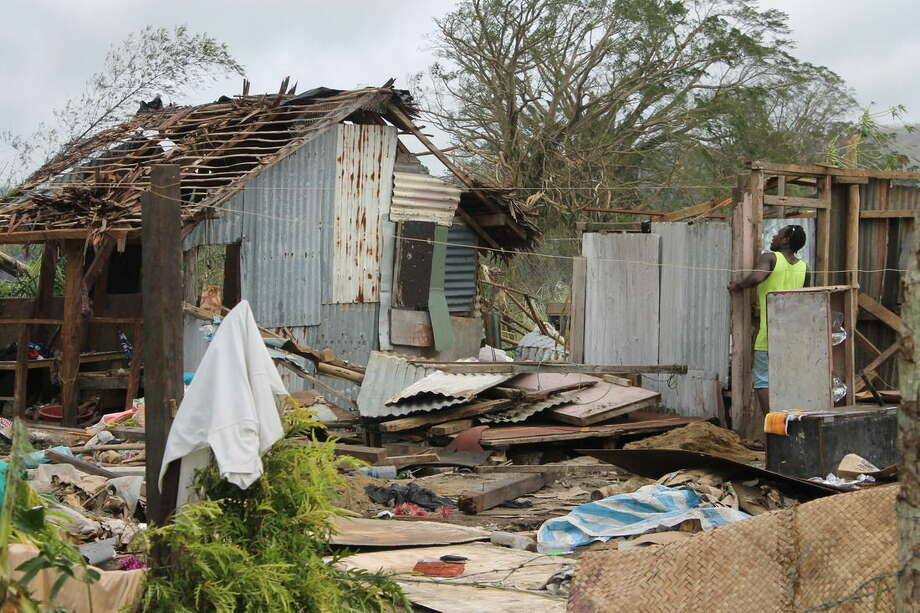 In this Tuesday, March 17, 2014, photo provided by UNICEF Pacific, a man looks into the remains of a house in the wake of Cyclone Pam. When Cyclone Pam ripped across the tiny South Pacific island nation of Vanuatu, there were fears its monstrous winds could kill thousands. But as aid workers finally reached the archipelago's hard-hit outer islands on Wednesday, it appeared that residents' familiarity with disasters and careful planning had spared the lives of most. (AP Photo/UNICEF Pacific) EDITORIAL USE ONLY, NO SALES