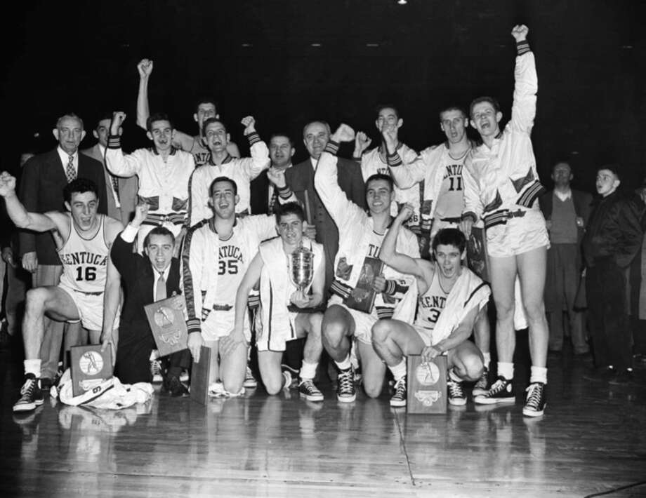FILE - In this March 27, 1951, file photo, the Kentucky basketball team celebrates winning the NCAA college basketball championship after defeating Kansas State 68-58 in Minneapolis. In 1939, the national title was decided by an eight-team competition. In 2015, 68 teams will play in 14 venues across the country, every game will be on TV, and the championship game will be played in an NFL stadium while millions of people watch across the country and around the world. (AP Photo/Chet Magnuson, File)