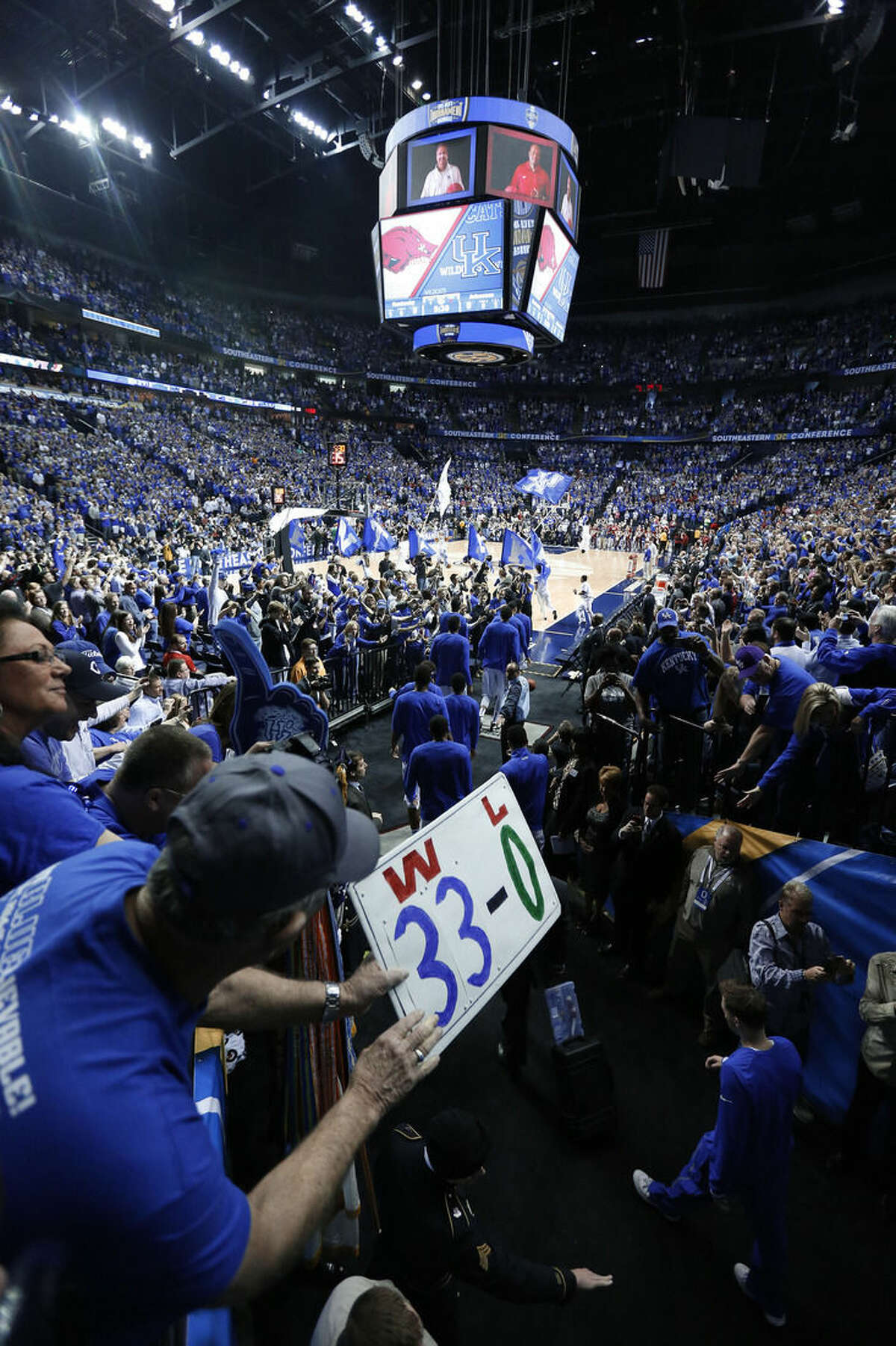 FILE - In this Sunday, march 15, 2015, file photo, a Kentucky fan cheers as the team steps on to the court for the first half of the NCAA college basketball against Akransas in the championship of the the Southeastern Conference tournament in Nashville, Tenn. In 1939, the NCAA national title was decided by an eight-team competition. In 2015, 68 teams will play in 14 venues across the country, every game will be on TV, and the championship game will be played in an NFL stadium while millions of people watch across the country and around the world. (AP Photo/Steve Helber, File)