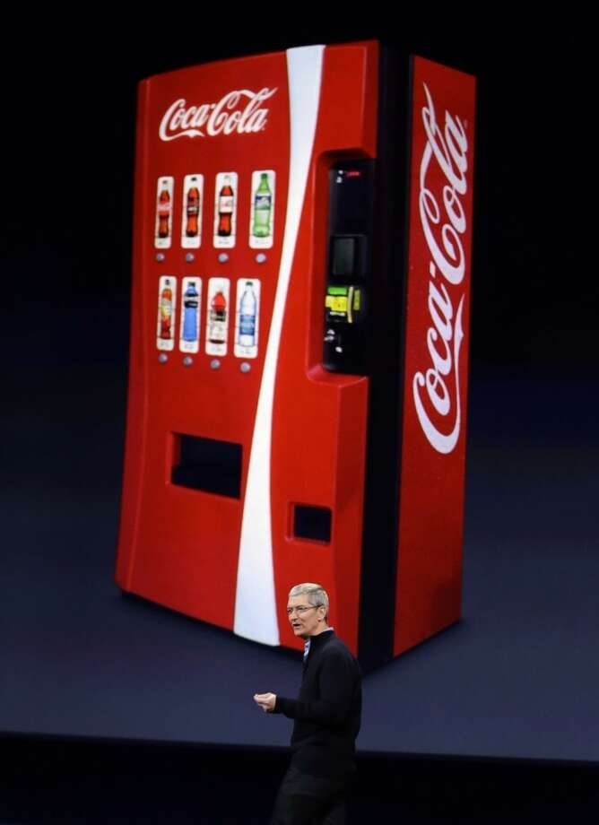 Apple CEO Tim Cook talks about using Apple Pay with Coca-Cola vending machines, during an Apple event on Monday, March 9, 2015, in San Francisco. (AP Photo/Eric Risberg)