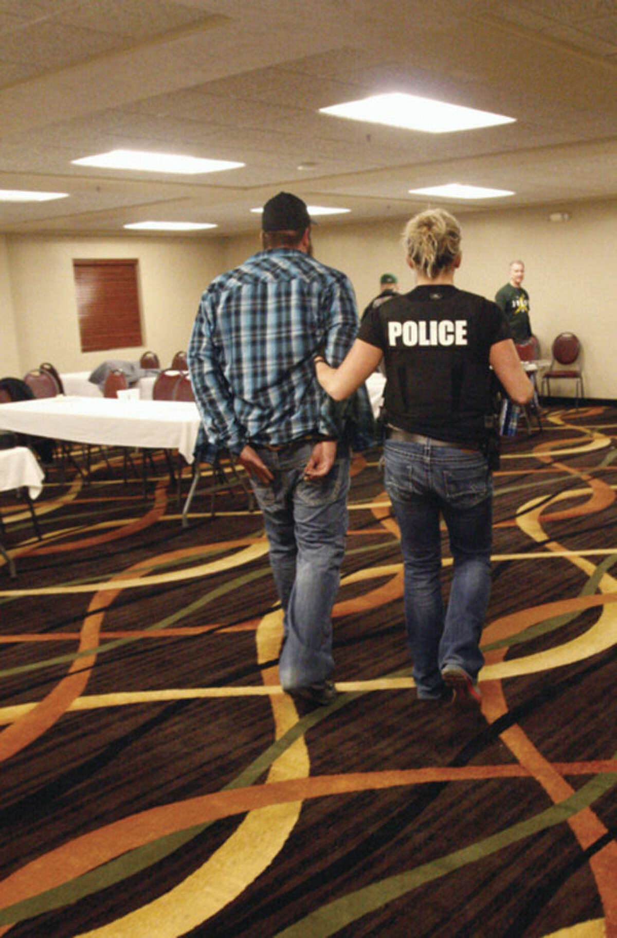 AP photo/Martha Irvine A police officer escorts a man arrested for prostitution solicitation at a hotel in Minot, N.D., in the early morning hours of Saturday, Jan. 31. Sex trafficking has become a big problem in North Dakota amid an oil boom that has brought in money and oil workers. The Minot police sting ended with the arrests of 13 men, who answered ads on an escort website posted by the undercover officers.