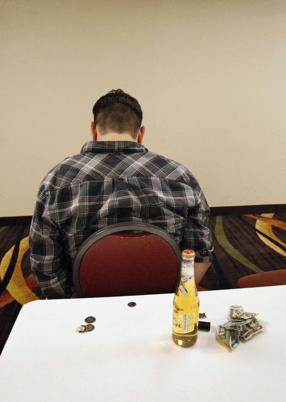ADVANCE FOR USE MONDAY, MARCH 9, 2014 AND THEREAFTER - With a beer he had in his back pocket on a table with other posessions, a man arrested for prostitution solicitation waits to be booked at a hotel in Minot, N.D., in the early morning hours of Saturday, Jan. 31, 2015. Sex trafficking has become a big problem in North Dakota amid an oil boom that has brought in money and oil workers. The Minot police sting ended with the arrests of 13 men, who answered ads on an escort website posted by the undercover officers. (AP Photo/Martha Irvine)