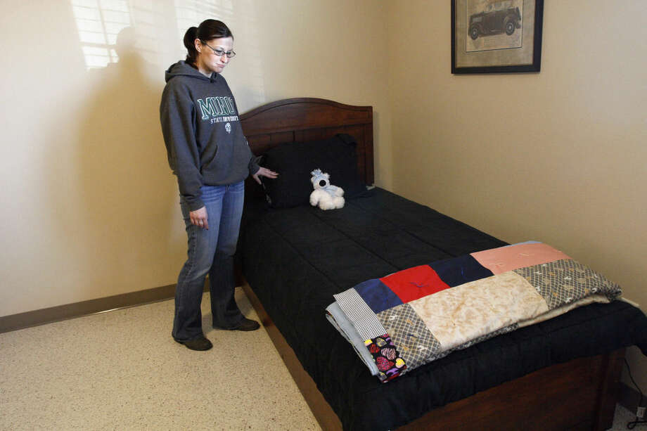 ADVANCE FOR USE MONDAY, MARCH 9, 2014 AND THEREAFTER - In this Friday, Jan. 30, 2015 photo, Tara Bjornson, assistant director of the Domestic Violence Crisis Center, stands by a bed in an unoccupied room at the center's emergency shelter in Minot, N.D. Sex trafficking has become a big problem in North Dakota amid an oil boom that has brought in money and oil workers - and Bjornson said the shelter has seen an increase in sex trafficking victims at its facility in the past year. (AP Photo/Martha Irvine)