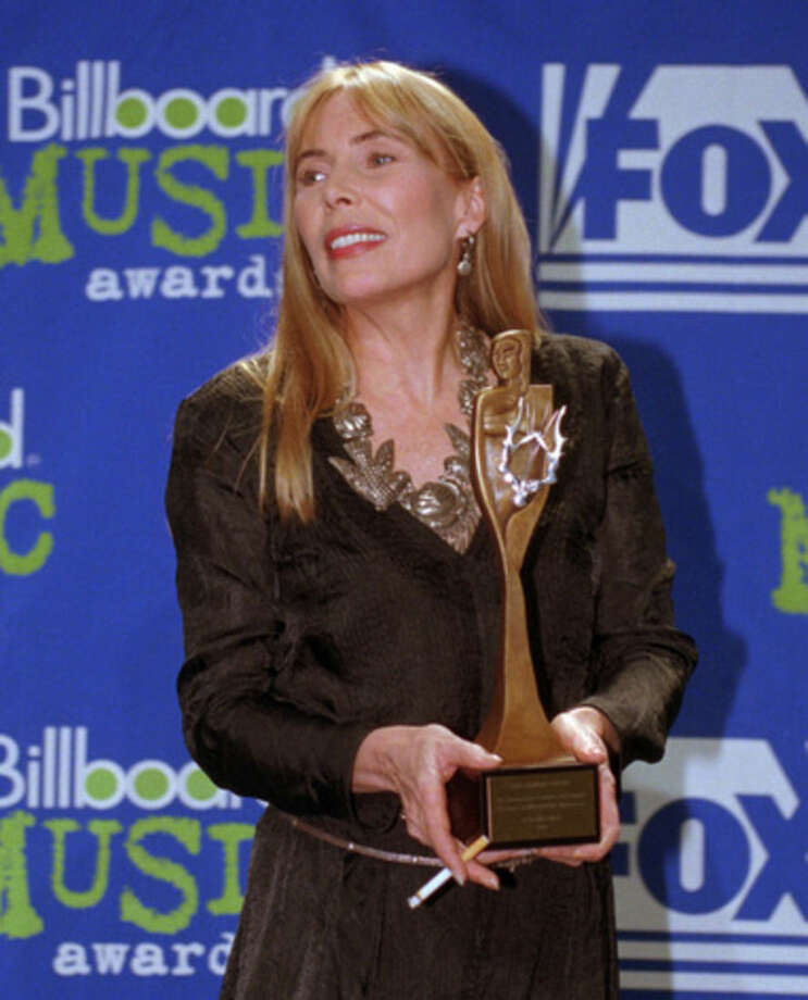 In this Dec. 6, 1995 file photo, singer/songwriter Joni Mitchell poses with the Century Award at the 1995 Billboard Music Awards in New York. Mitchell was hospitalized in Los Angeles on Tuesday, March 31, 2015 according to the Twitter account and website of the folk singer and Rock and Roll Hall of Famer, but details on her condition have not been released. (AP Photo/Adam Nadel, File)