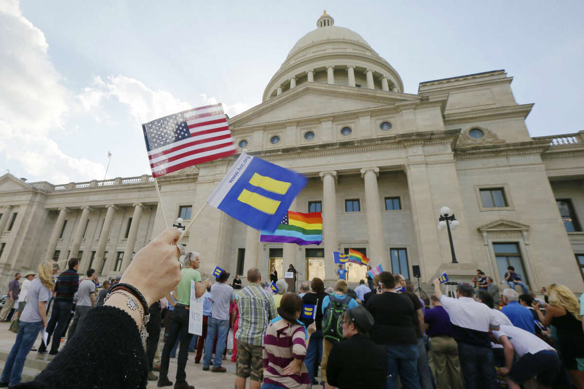 Demonstrators wave flags as they attend a rally at the Arkansas state Capitol in Little Rock, Ark., Tuesday, March 31, 2015, in protest of a bill passed by the state House critics say will lead to discrimination against gays and lesbians. (AP Photo/Danny Johnston)