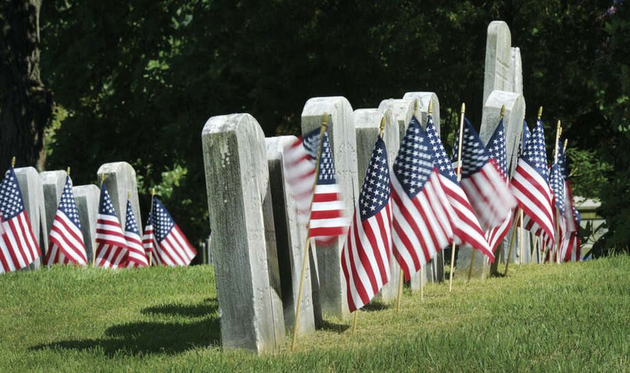 Hour File photo/Alex von KleydorffUnder bright skies, flags wave in the wind in front of rows of veterans' headstones in Riverside cemetery.