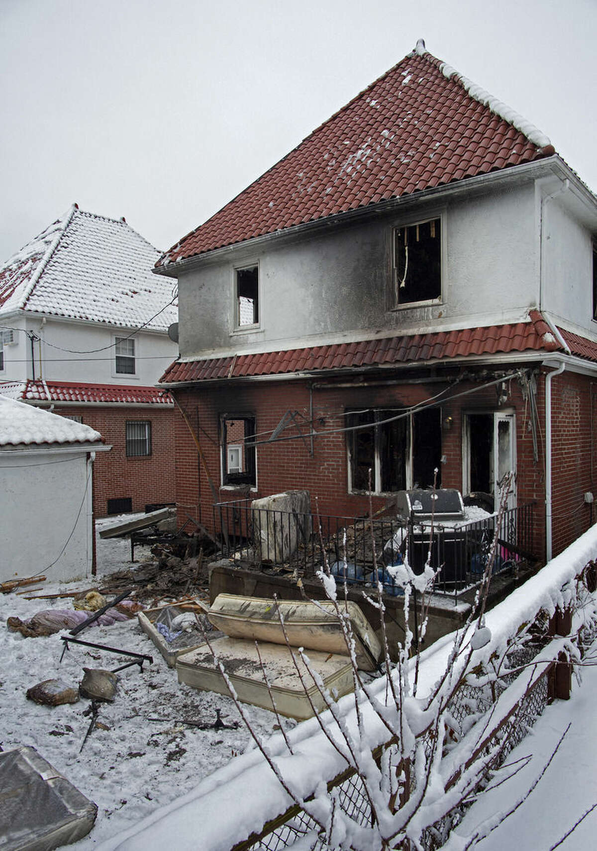 Debris lay scattered behind the house at the scene of a fire in the Brooklyn borough of New York Saturday, March 21, 2015. The fire raged through the residence early Saturday, killing seven children and leaving two other people in critical condition, authorities said. (AP Photo/Craig Ruttle)