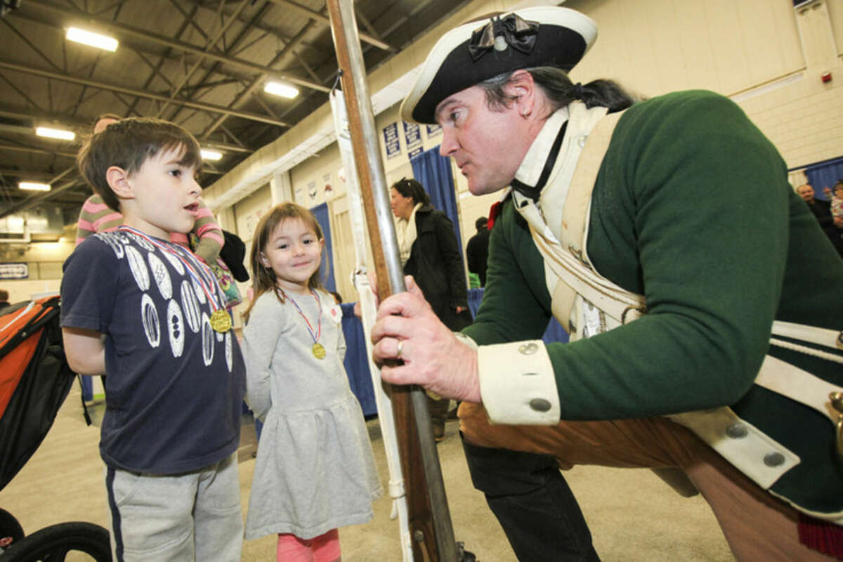 Hour photo/Chris Palermo. Walt Matis of the Fairfield Museum talks to Julianne Palmer, 4, and her brother John, 6, at the Kids Fest at the Wilton High School Fieldhouse Sunday.