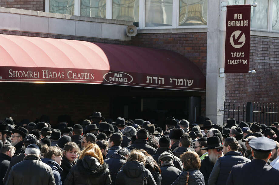 Mourners gather outside of Shomrei Hadas Chapels before a funeral service for the seven siblings killed in a house fire, Sunday, March 22, 2015, in the Brooklyn borough of New York. The siblings, ages 5 to 16, died early Saturday when flames engulfed the Sassoon family home in the Midwood neighborhood of Brooklyn. Investigators believe a hot plate left on a kitchen counter set off the fire that trapped the children and badly injured their mother and another sibling. (AP Photo/Julio Cortez)