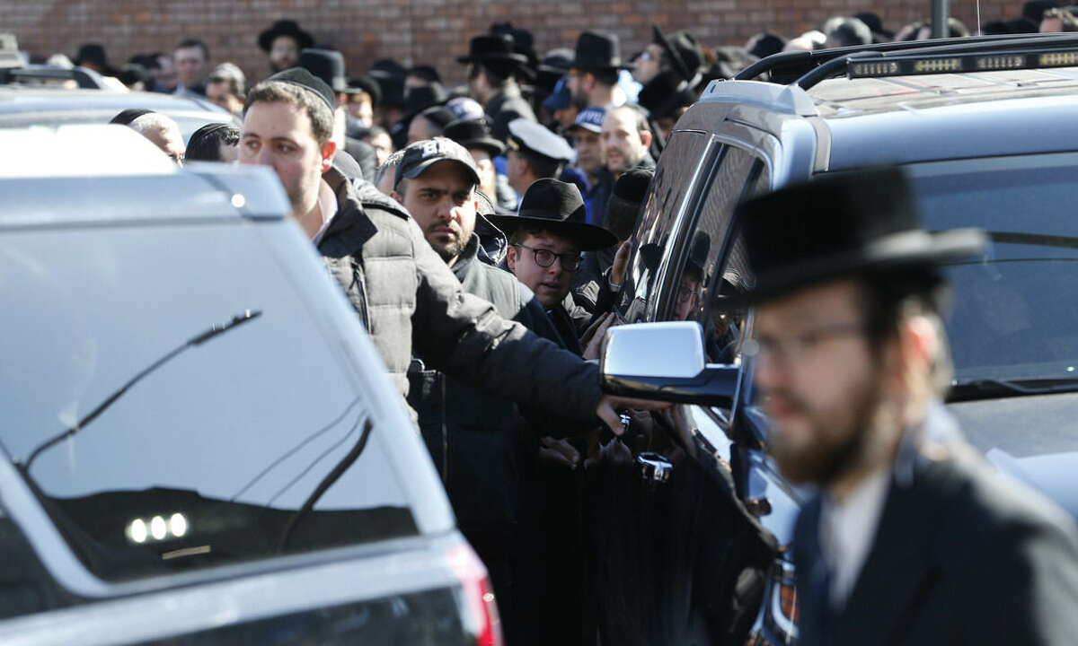 Mourners follow closely behind a vehicle containing the remains of the seven siblings who died in a house fire leaving Shomrei Hadas Chapels following funeral services, Sunday, March 22, 2015, in the Brooklyn borough of New York. The siblings, ages 5 to 16, died early Saturday when flames engulfed the Sassoon family home in the Midwood neighborhood of Brooklyn. Investigators believe a hot plate left on a kitchen counter set off the fire that trapped the children and badly injured their mother and another sibling. (AP Photo/Julio Cortez)