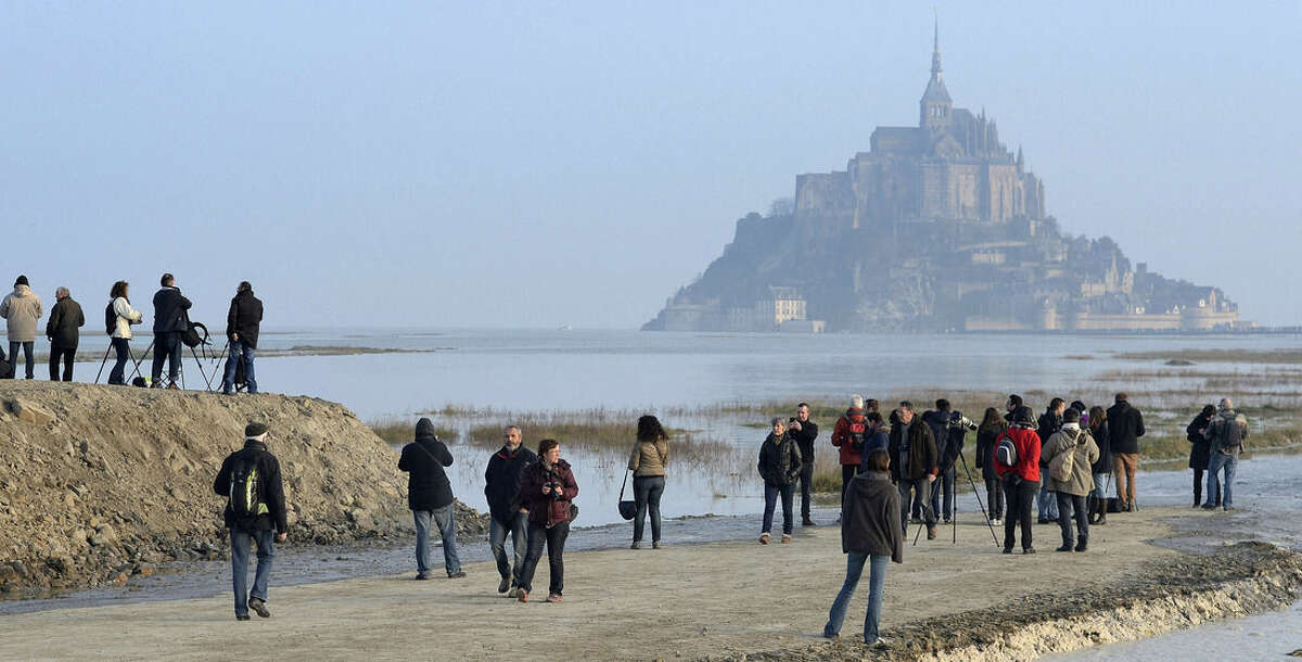 """People gather ahead of a high tide submerging a narrow causeway leading to the Mont Saint-Michel, on France's northern coast, Saturday, March 21, 2015. A supertide has turned France's famed Mont Saint-Michel into an island and then retreated out of sight, delighting thousands of visitors who came to see the rare phenomenon. The so-called """"tide of the century"""" actually happens every 18 years (AP Photo)"""