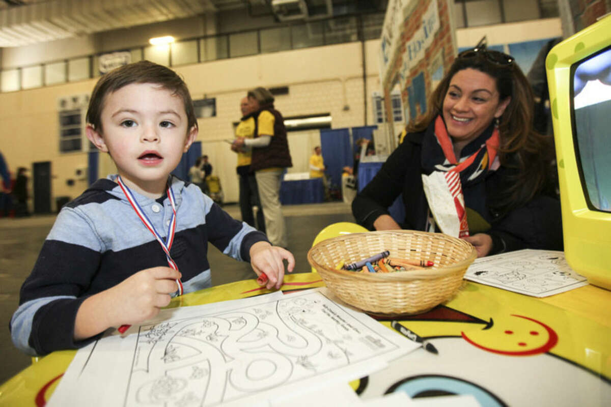 Hour photo/Chris Palermo Christopher Millin, 2, of Wilton, colors with his mother at the Kids Fest at the Wilton High School Fieldhouse Sunday.