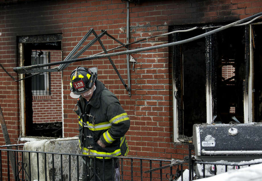 An FDNY firefighter looks over the scene of a house fire Saturday, March 21, 2015, in the Brooklyn borough of New York. The fire raged through the residence early Saturday, killing seven children and leaving two other people in critical condition, authorities said. (AP Photo/Craig Ruttle)