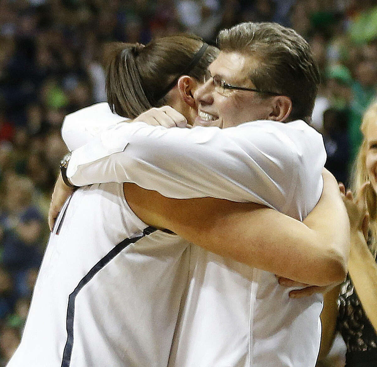 FILE - In this April 18, 2014, file photo, Connecticut center Stefanie Dolson (31) embraces Connecticut head coach Geno Auriemma during the second half of the championship game against Notre Dame in the Final Four of the NCAA women's college basketball tournament in Nashville, Tenn. Auriemma and the UConn Huskies have turned women's college basketball into their own showcase. Over the past two decades, the Hall of Fame coach and his players have been the face of the sport, winning nine championships and poised to make a run at a 10th title. (AP Photo/John Bazemore, File)