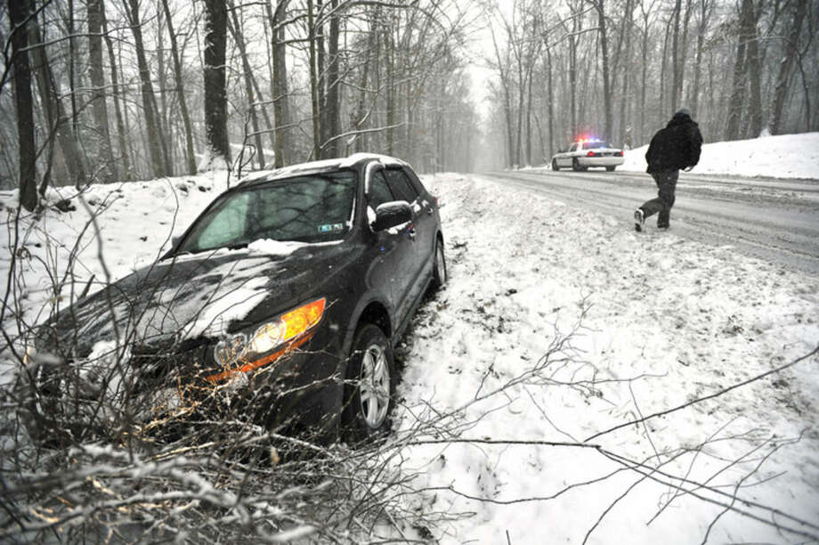 The driver of a vehicle runs over to talk to a Patton Twp. police officer after his vehicle slid off the road Friday, March 20, 2015, in State College, Pa. Forecasters say a storm will dump up to 6 inches of snow on the Northeast and mid-Atlantic on Friday. New England will be on the lower end of the snow totals but even Boston, which has seen a record 108.6 inches of snow, could get an inch or more. (AP Photo/Centre Daily Times, Nabil K. Mark) MANDATORY CREDIT; MAGS OUT